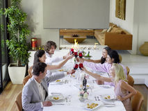 Friends Toasting Wineglasses Across Dinner Table Stock Photo