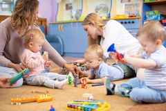 Friends with toddlers playing on the floor in montessori centre. Friends with children toddlers playing on the floor in montessori centre stock photos