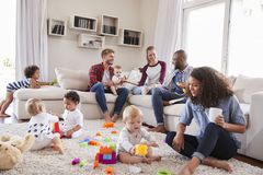 Friends with toddlers playing on the floor in sitting room stock photo