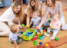 Friends with toddlers playing on the floor in sitting room. Female friends with toddlers playing on the floor in sitting room stock image