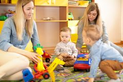 Friends with toddlers playing on the floor in sitting room. Female friends with babies toddlers playing on the floor in sitting room royalty free stock image