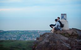 Friends on top of the mountain. Shoot in Edinburgh, UK, two friends sit on top of the mountain Royalty Free Stock Photos
