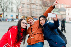 Friends in a touristic city center, taking a selfie. Three happy friends in a touristic city center, taking a self portrait  with wearable camera while visiting Stock Photo