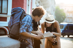 Friends travelers with backpacks smiling, looking route at map in the street. Stock Photo