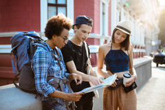 Friends travelers with backpacks smiling, looking route at map in the street. Stock Photos