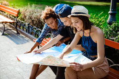 Friends travelers smiling, looking route at map, sitting on bench. Royalty Free Stock Photo