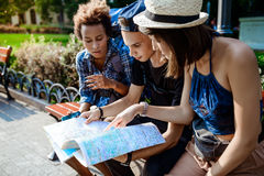 Friends travelers smiling, looking route at map, sitting on bench. Stock Photos