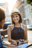 Friends travelers smiling, speaking, holding map outside. Street background. stock photos
