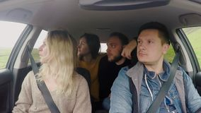 Friends traveling by car together and listening the music. Group of young people dancing, having fun inside the vehicle. stock footage