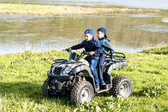 Friends are traveling by quad bike along the river bank royalty free stock image