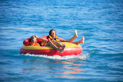 Friends Tubing On Sea Stock Image