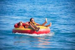 Friends Tubing On Sea Stock Image