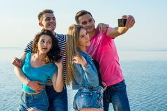 Friends - two guy and two women, brunette and blonde - laugh and. Young people - two guy and two women, brunette and blonde - laugh and do selfie by the seashore Stock Photography
