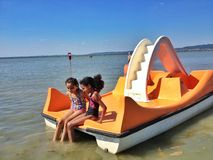 Summer vacation. Two lovely kids on summer vacation sitting in a boat at Lake Balaton, Hungary royalty free stock image