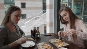 Friends Two young women met at a cafe, business lunch. Talk and eat fish in batter. Knife and fork, smile stock footage