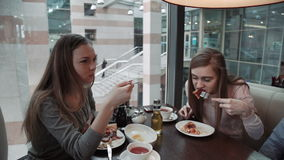 Friends two young women met at a cafe, business lunch. Talk and eat Italian pizza. Knife and fork, smile stock video footage
