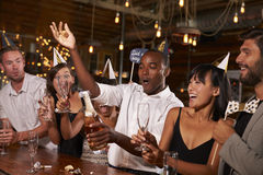 Free Friends Uncorking Champagne At A New Year�s Party At A Bar Royalty Free Stock Image - 85191856