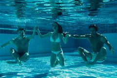 Friends under water in swimming pool Royalty Free Stock Image