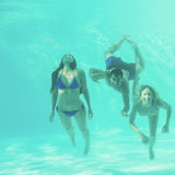 Friends underwater in swimming pool Stock Photos