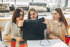 Friends unpacking new clothes. Shopping day. Friends unpacking new clothes sitting at coffee-shop in the mall. Shopping day, fashion, sale, friendship, hobby Royalty Free Stock Images