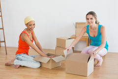 Friends unwrapping boxes in a new house Stock Image