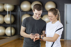 Friends Using Cell Phone And Wearable In Gym. Smiling young male and female friends using cell phone and wearable in gym Royalty Free Stock Images