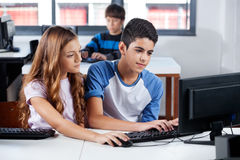 Friends Using Desktop Pc In School Lab Royalty Free Stock Images