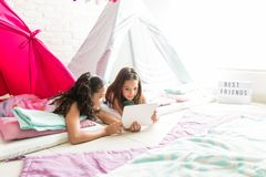 Friends Using Internet On Tablet Computer While Resting In Teepe. Preteen best friends using internet on tablet computer while resting in teepee at home royalty free stock photos