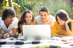 Friends using laptop outdoors Royalty Free Stock Photo