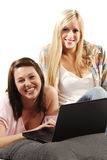 Friends using laptop smiling at the camera Royalty Free Stock Images