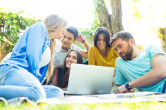 Friends using laptop together outdoors Royalty Free Stock Images