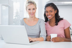 Friends using laptop together and smiling at camera Stock Photos