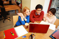 Friends using laptop together. Young happy friends using laptop together Royalty Free Stock Image