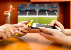 Betting in football. Friends using mobile phone and betting during a football or soccer match Stock Photos