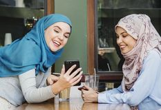 Friends using mobile phone together royalty free stock images