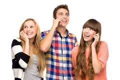 Friends using mobile phones. Three young people over white background Royalty Free Stock Photo