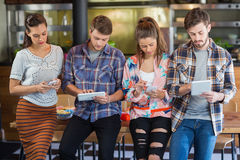 Friends using mobile phones and digital tablets. While standing in restaurant royalty free stock photos