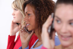 Friends using mobile telephones Royalty Free Stock Photography