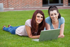 Friends using a notebook. While lying on the lawn Stock Photography