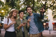 Friends using smartphone for find a way in city. Group of friends on city tour using mobile phone for navigation. Three young people exploring a city using smart Stock Photo