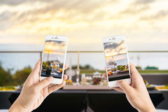 Friends using smartphones to take photos of empty glasses set in Stock Images