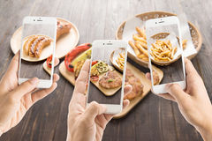 Friends using smartphones to take photos of sausage and pork cho Royalty Free Stock Photo