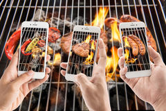 Friends using smartphones to take photos of sausage and pork chop and vegetables on the flaming grill.  stock image