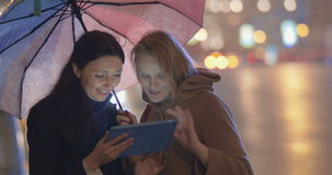 Friends Using Tablet PC Outdoors. Two female friends are standing outdoor, watching something in tablet PC and discussing it lively. Road traffic is on the stock video footage