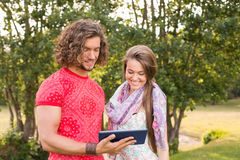 Friends using tablet pc in the park Stock Image