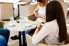 Friends using their mobile phones and ignoring each other while sitting at cafe stock photo