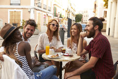 Friends on vacation laughing outside a cafe in Ibiza Stock Images