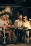 Friends vapor hookah and drink alcohol in bar lounge. Twins women and men relax in shisha cafe outdoor. Addiction, bad habits. Celebration, party concept Stock Image