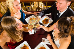 Friends in a very good restaurant clink glasses Stock Images