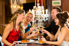 Friends in a very good restaurant clink glasses. Good friends for dinner or lunch in a fine restaurant, clinking glasses Royalty Free Stock Image